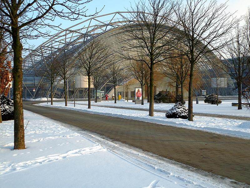 Leipziger Messe im Winter mit Schnee und kahlen Bäumen